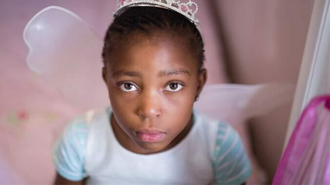 Uma menina vestida de fada olhando com olhos triste para cima