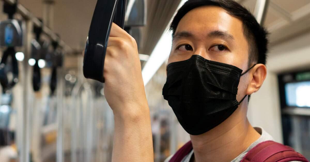 Homem usando máscara facial no transporte público.