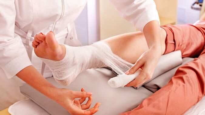 Um profissional de saúde fazendo uma bota de unna em um paciente