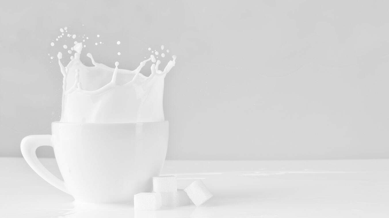Xícara com leite e cubos de açúcar ao lado.