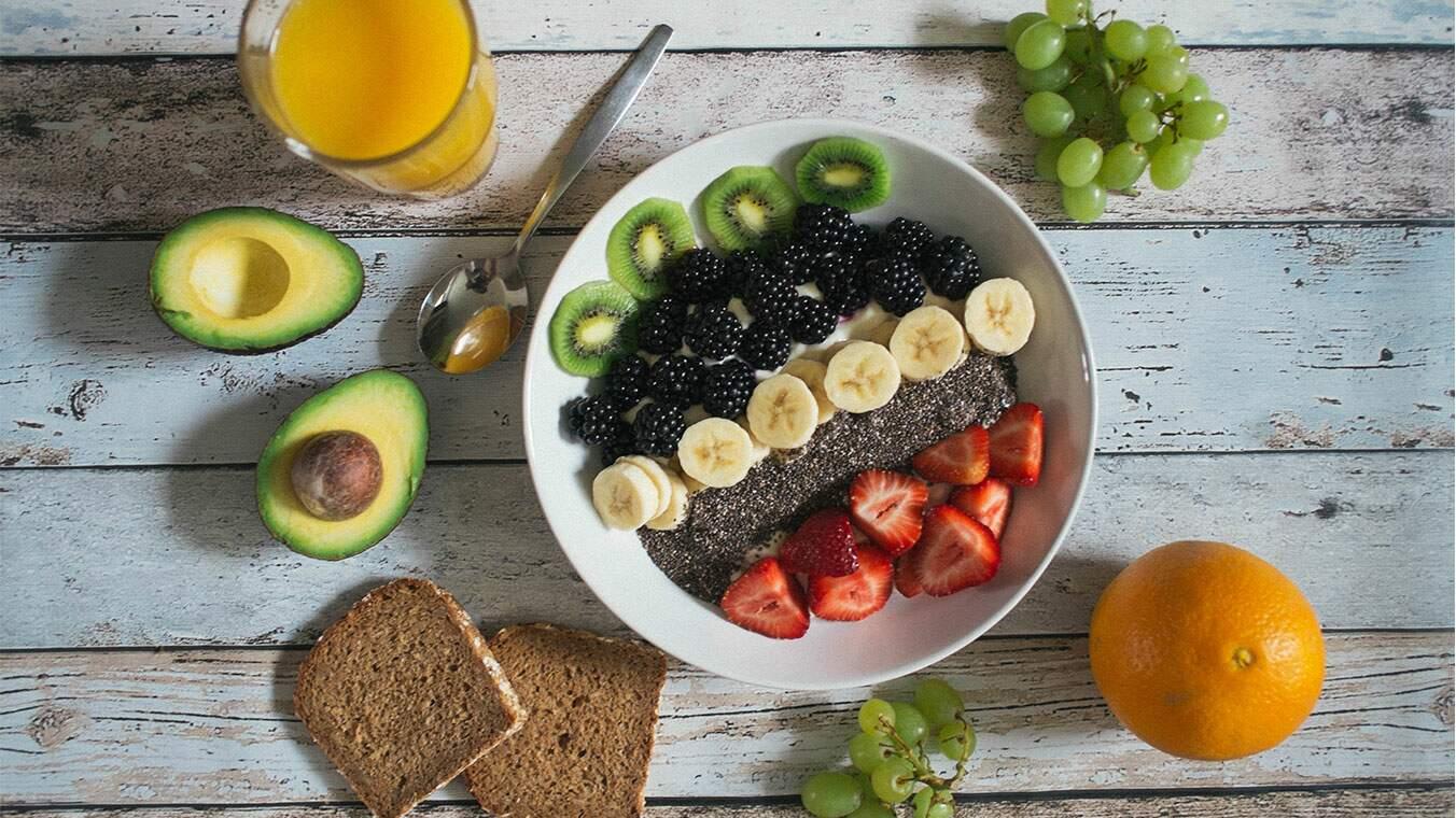 Uma mesa com frutas, sucos e pão
