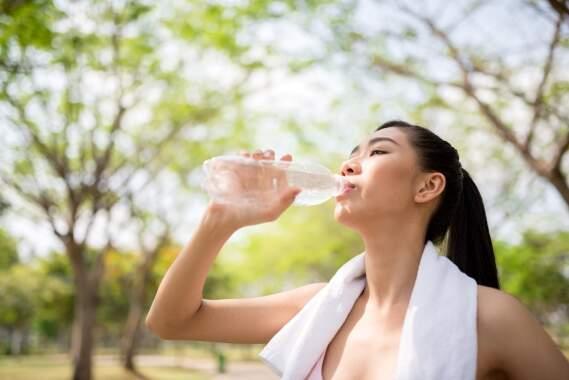 Uma mulher com uma toalha no pescoço, bebendo água em uma garrafa PET