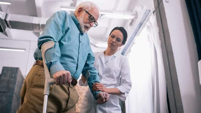 Um senhor idoso se apoiando em uma muleta para ficar em pé, sendo auxiliado por uma enfermeira