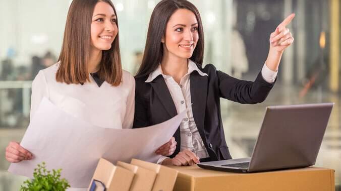 Duas mulheres, uma mexendo em um computador, e outra com um papel na mão