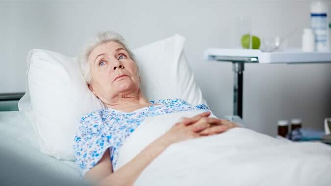Uma idosa deitada em uma cama olhando para algum lugar, ao redor um móvel com remédios e outros itens