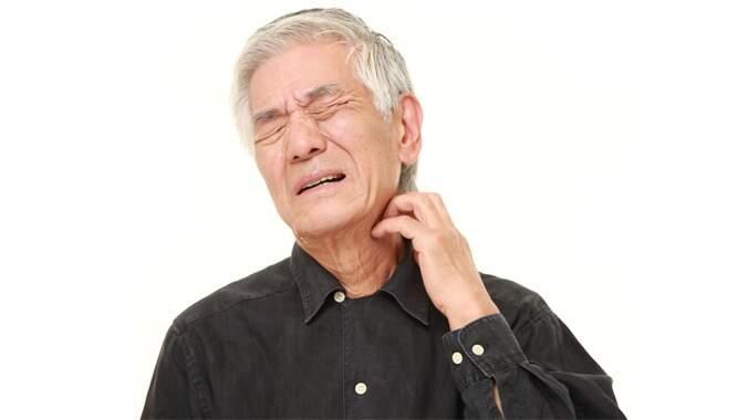Um senhor com a mão no pescoço e semblante de dor