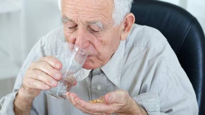 Um senhor idoso tomando um comprimido com um copo de água na mão