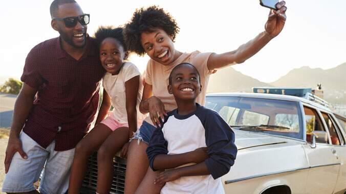 Uma família sentada na frente de um carro tirando um foto