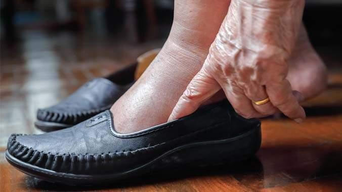 Uma pessoa idosa calçando um par de sapatos mocassim na cor preta